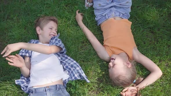 Cover Image for Portrait Two Fun Cute Adorable Kids Lying on the Grass in the Park Smiling To Each Other. Funny Girl