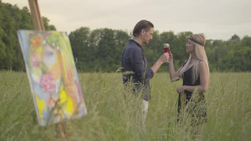 Romantic Creative Couple Drinking Wine and Talking with Blurred Artwork Standing at Front. Portrait