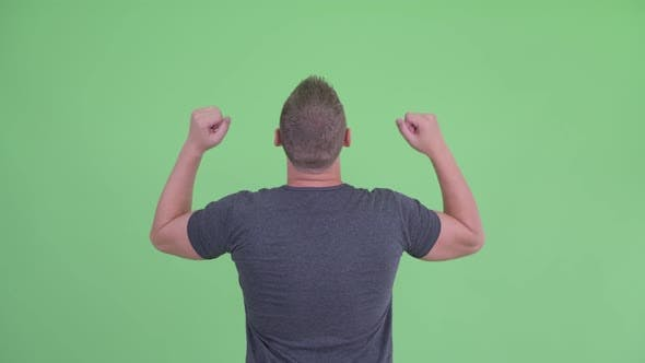 Thumbnail for Rear View of Happy Young Man with Fists Raised