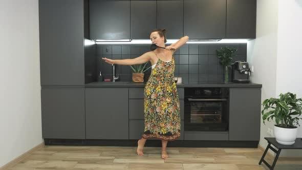 Thumbnail for Fröhliche und hübsche Frau tanzt und singt mit Küchenlöffel in der modernen Wohnküche