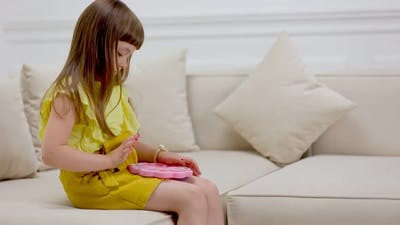 Girl Playing with a Toy Pop It