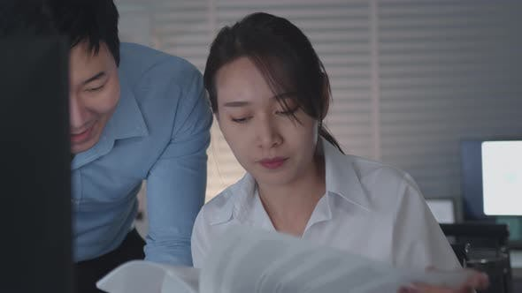 Asian Businessman and Businesswoman looking at desktop computer screen discussing  a business