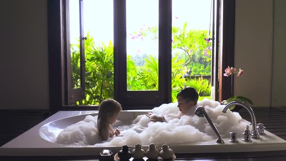 Thumbnail for Child Boy and Girl Bathe in a Large White Bath with Foam and Big Window with Tropical Green Garden