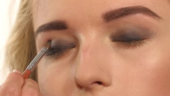 Thumbnail for Make-up Artist Applying Bright Base Color Eyeshadow on Model's Eye and Holding a Shell with