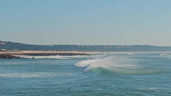 People swimming on surfing boards in the ocean near the Lisbon coast, Portugal