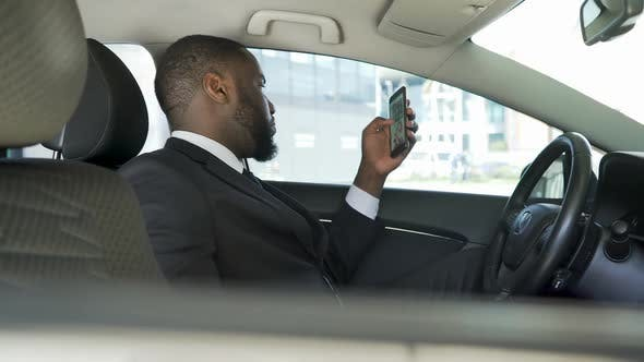 Thumbnail for Driver Waiting for Boss, Bored Scrolling News Application on His Smartphone