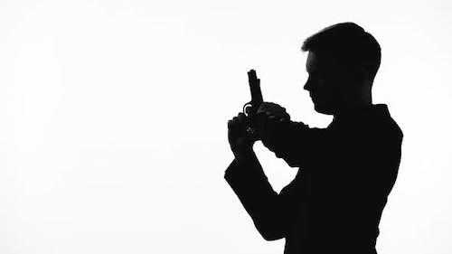 Silhouette eines kaltblütigen Killers, der auf Handfeuerwaffe, Rache, Auftragsmord zeigt