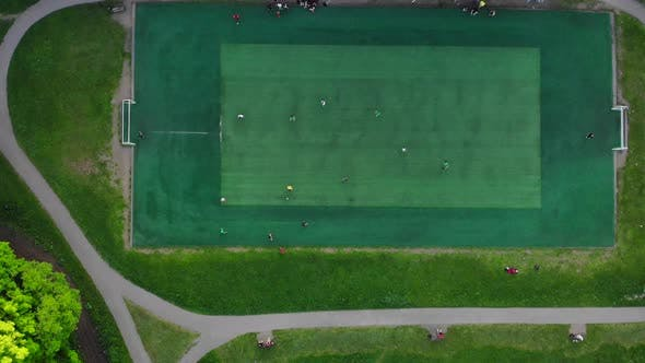 Aerial View of Men Playing Football on a Public City Soccer Field