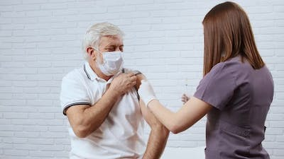 Female Doctor or Nurse Giving Vaccine for Patient