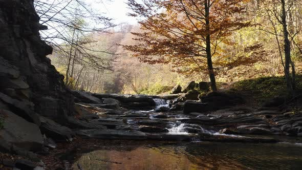 Thumbnail for Water flowing over shaded rocks