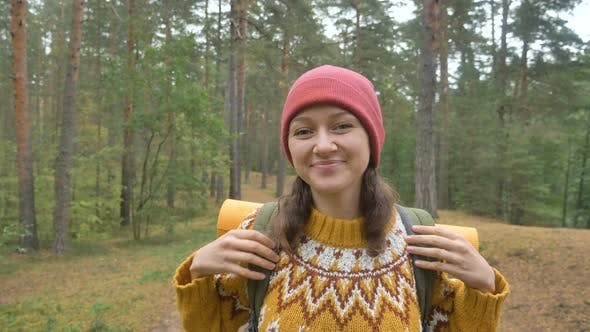 Thumbnail for Lady in Knitted Sweater Red Hat Poses in Evergreen Forest