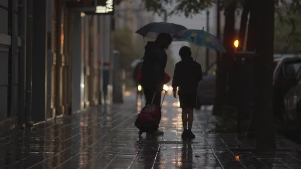 Mom and Son Walking in the Street Under the Rain