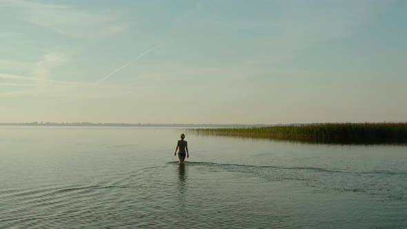 Thumbnail for Aerial Drone View, Attractive Young Woman Walking in a Lake at Summer Day