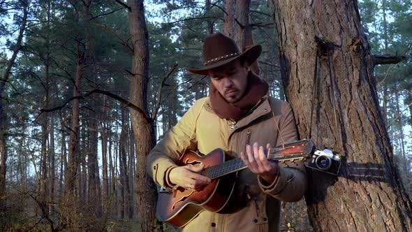Thumbnail for A Backpacker in a Hat with a Guitar in the Forest