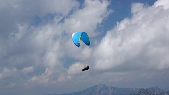 Thumbnail for Paraglider and Clouds over the Mountains