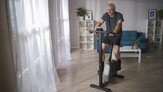 Thumbnail for Grey Haired Man Is Training on Spinning Bike in Living Room Healthy Lifestyle at Middle Age
