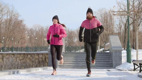 Slow Motion Fit Couple Jogging in Winter