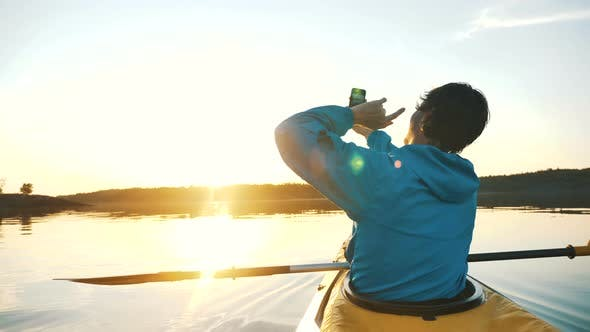 Thumbnail for Man Makes Selfie on Smartphone While Sitting in Kayak on Calm Lake at Sunset, Outdoor Activities