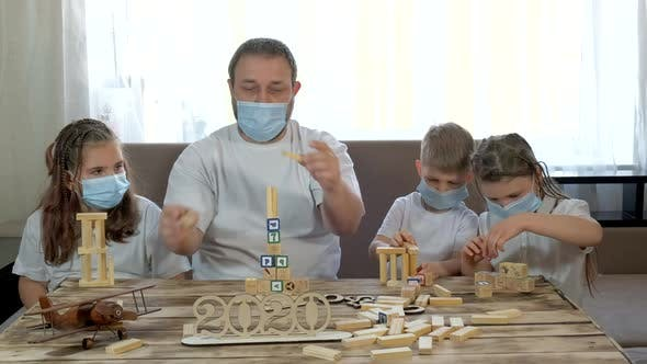 Dad and Kids Play with Wooden Toys and Puzzles in the Room