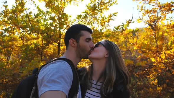 Portrait of Happy Smiling Couple Kisses While Takes Selfie Photo with Autumn Garden at Background