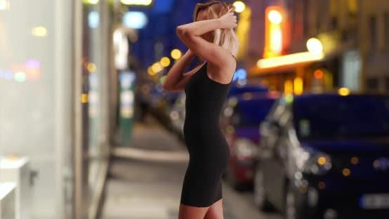 Elegant Caucasian female in her 30s wearing black dress dancing in city street