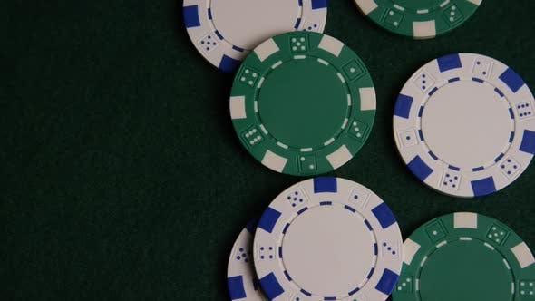 Rotating shot of poker cards and poker chips on a green felt surface - POKER 041