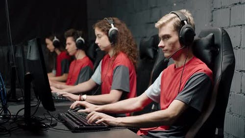 Young Gamers in Headphones, Plays a Video Game, Cyber Sportsman at the Game, Communication Between