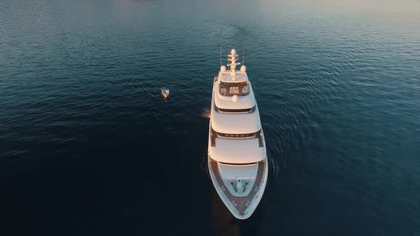 A stunning aerial view of huge luxury yacht and small boat, south of France coast. Super yacht
