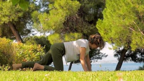 30 Years Old Woman Doing Fitness Exercises on Grass in Park