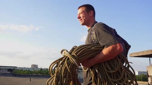 Professional Industrial Climber Walks Along the Roof with Rope Against Background of the Sun