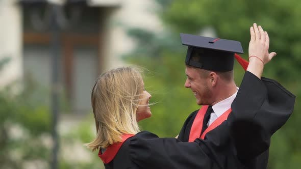 Cover Image for Beautiful Couple in Academic Dresses Hugging With Love and Laughing Cheerfully