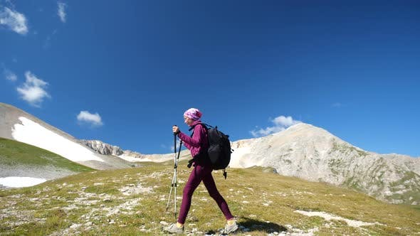 Thumbnail for Young Woman with Backpack and Trekking Poles Walks Uphill Towards the Summit. Slow Motion. Lady