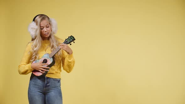 Thumbnail for Woman with Long Blonde Hair Wearing Earmuffs, Singing While Playing the Ukulele