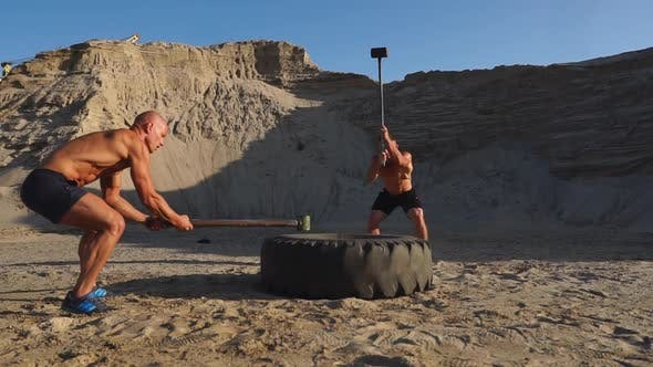Cover Image for Two Powerful Male Athletes Training Together Hit the Wheel with a Hammer at Sunset in the Desert
