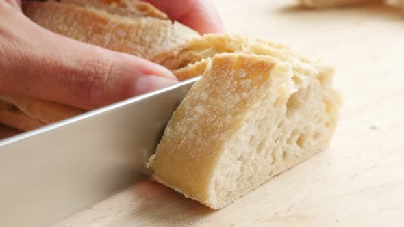 Thumbnail for Cutting  French bread bougette with a knife  close-up 4K 2160p UltraHD footage - French traditional