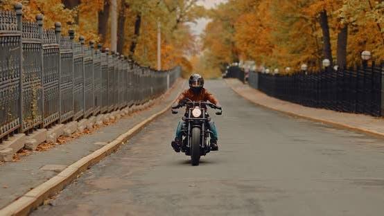 Coole Motorradfahrer fährt schnell auf einer Asphaltstraße. Herbstspaziergang auf einem coolen Bike.