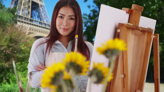 Thumbnail for Happy smiling Asian woman holding paintbrush near Eiffel Tower