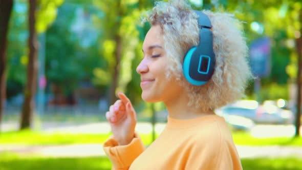 Thumbnail for Girl Using Bright Earphones Outdoor