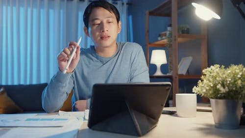 Asia freelance businessman focus work pen write on tablet computer busy with full of graph paperwork