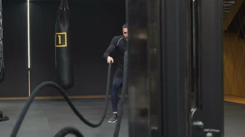 Athletic Young Man Changing Training Intensity with Battle Ropes