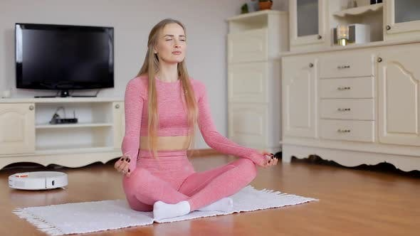 Thumbnail for Athletic girl in sportswear is doing yoga. Robot vacuum cleaner hoover gadget