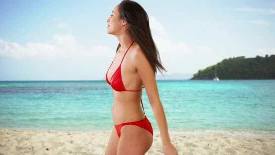 Thumbnail for A Hispanic girl plays around at the beach in her red bikini