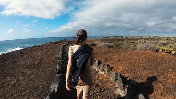 Woman Walks Along the Coastal Walkway Near the Ocean