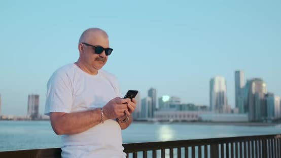 Cover Image for Bearded Senior Man Standing Outdoors Using Smartphone. Retired Male Reading News, Chatting