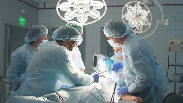 Thumbnail for Doctors Team in Surgery in a Dark Background