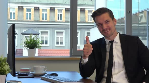 Thumbnail for An office worker in a suit sits at a desk in front of a computer and shows a thumb up to the camera