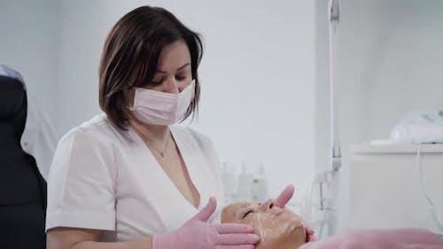 Kosmetikerin legt einer jungen Frau eine Membran mit Betäubungscreme auf das Gesicht