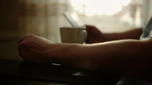 Mann sitzt an einem Tisch, trinkt Kaffee und benutzt ein Handy, Nahaufnahme, Fokuswechsel