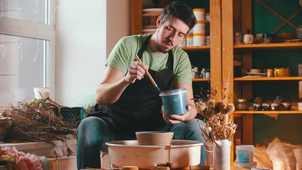Thumbnail for Pottery - the Master Is Painting a Bowl with Blue Paint