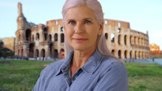 Casual portrait of happy retired mature woman near Coliseum smiling at camera
